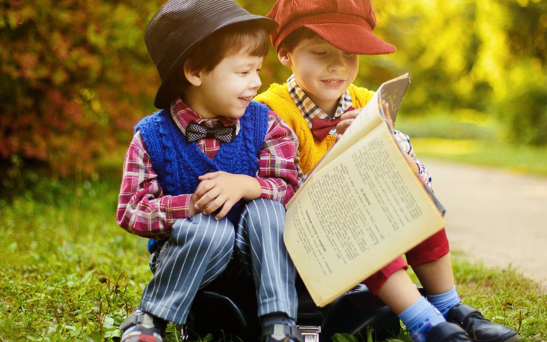 Grafika promująca czytanie wśród dzieci :Starszy chłopiec czyta młodszemu książeczkę.Napis: Książki dla dzieci online.